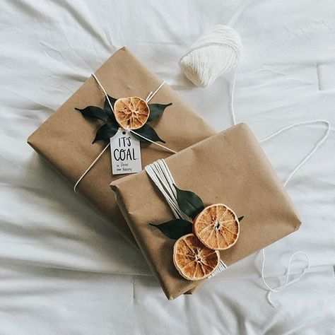 Image of presents wrapped in brown paper and decorated with dried oranges and string