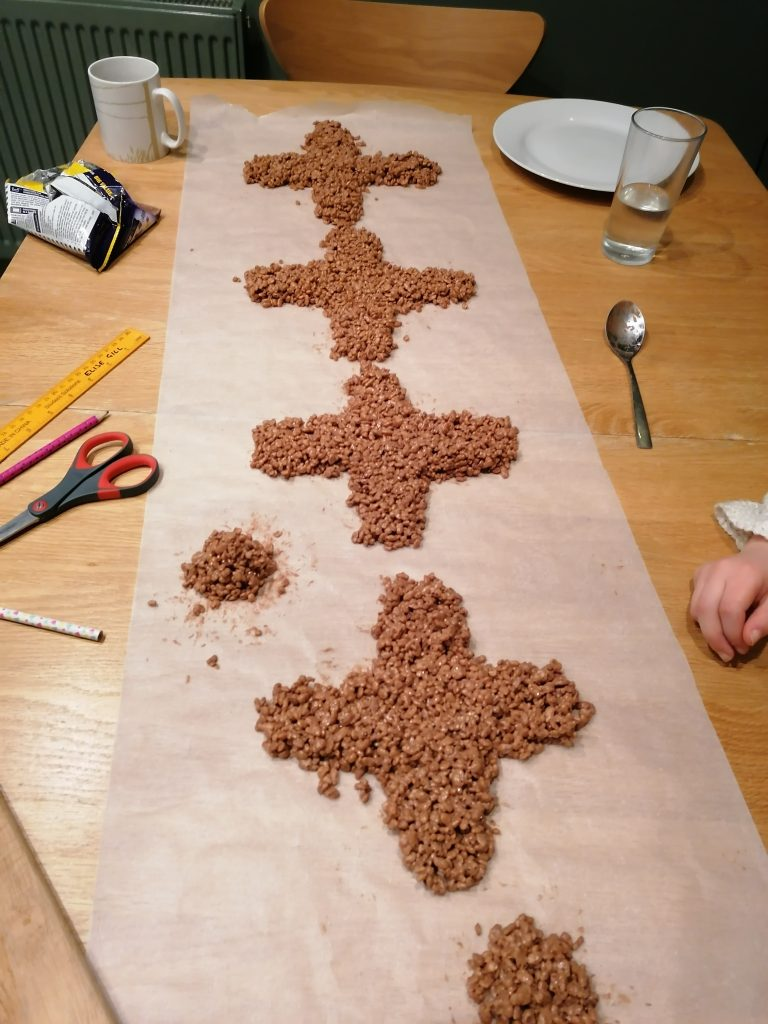 chocolate rice crispy crosses on parchment paper
