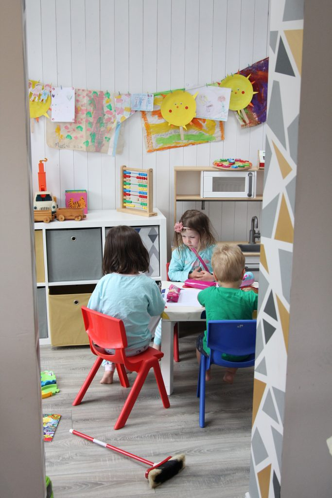 Geometric archway looking into the playroom with children at small table and chairs.