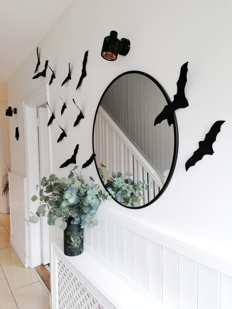 DIY Halloween decorations are black bats in a white hallway