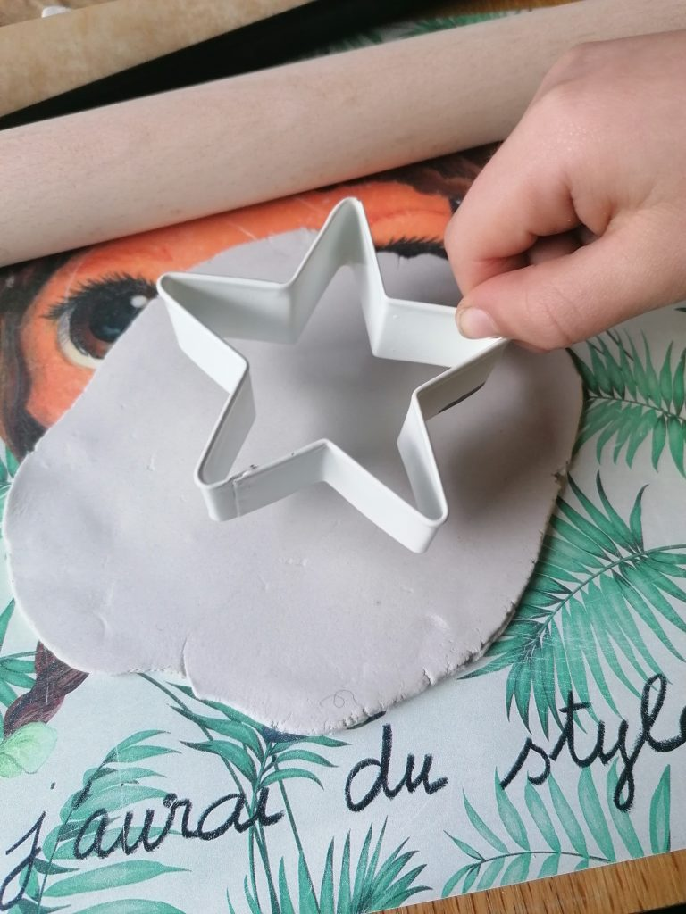rolled out air dry clay and a star cookie cutter