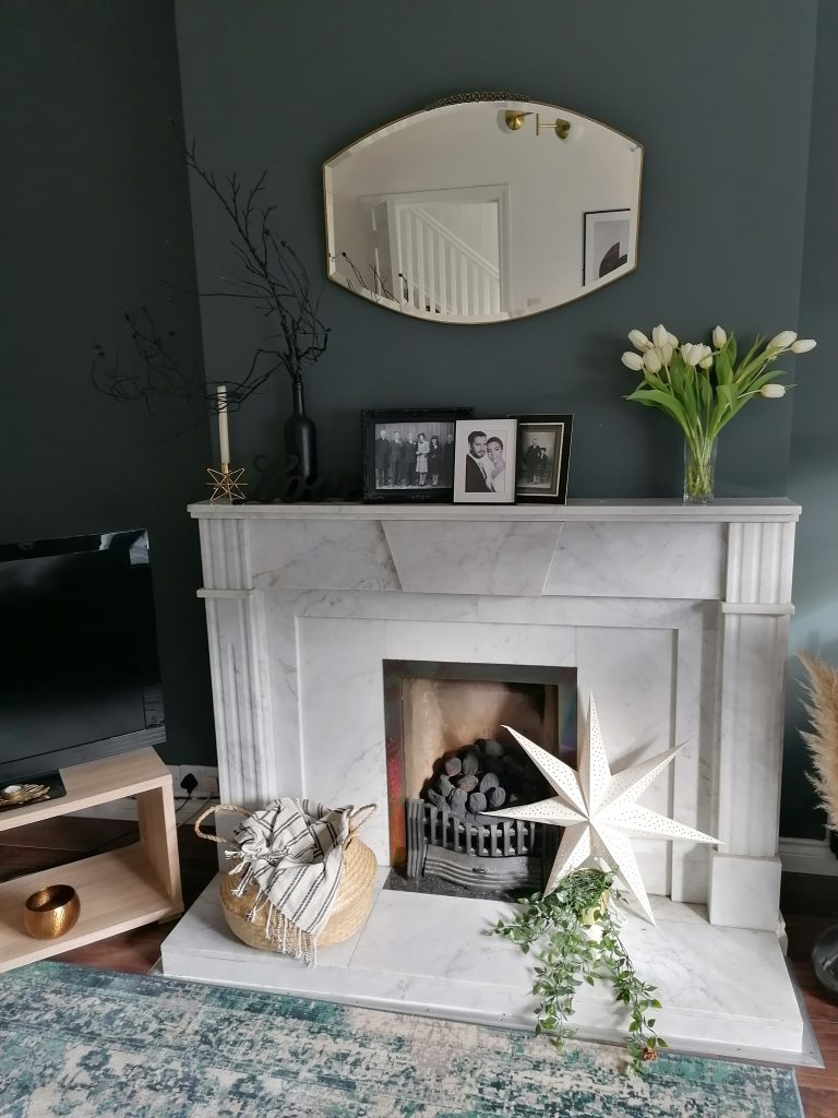 Sitting room with grey wall and tulips and mirror on the wall and large marble fireplace