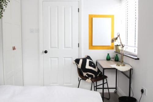 White walls and desk area, yellow paint around noticeboard