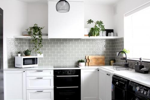 White and black kitchen, plants, black appliances