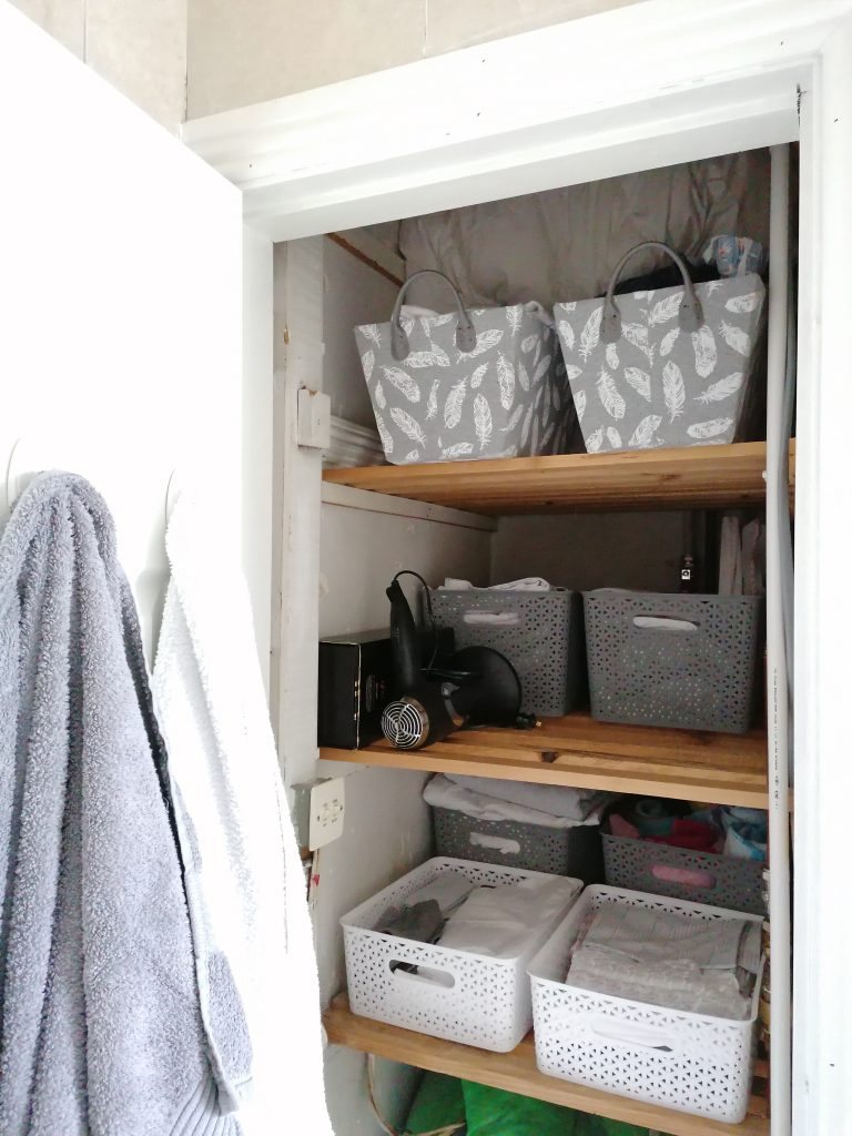 Grey and white towels to match the boxes in the organised hotpress
