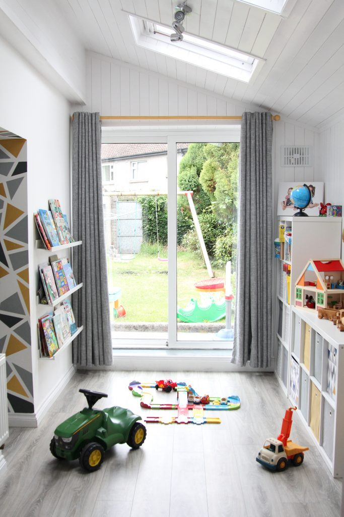 Playroom painted white and IKEA shelving for books and toys, adaptable and versatile for children