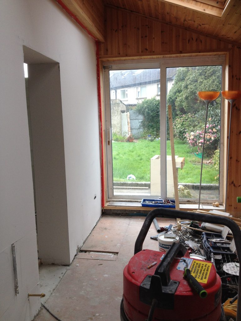 Conservatory with archway knocked into kitchen. No floor down.
