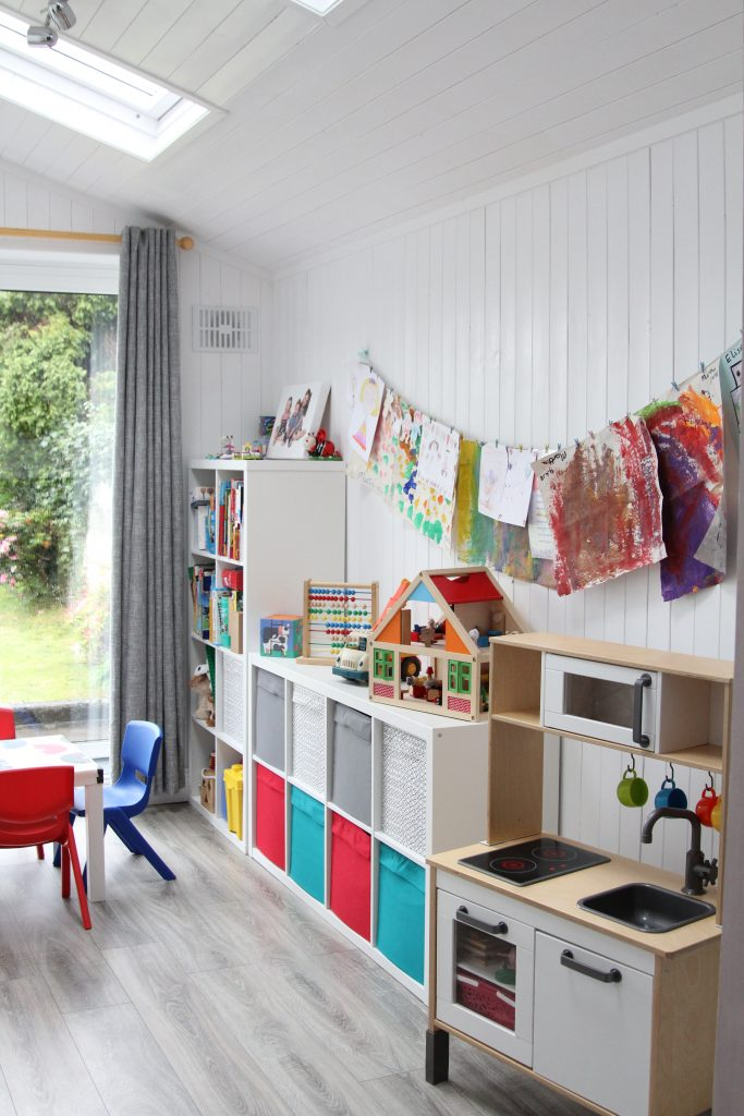 Childrens art on wall and IKEA storage unit and IKEA kitchen