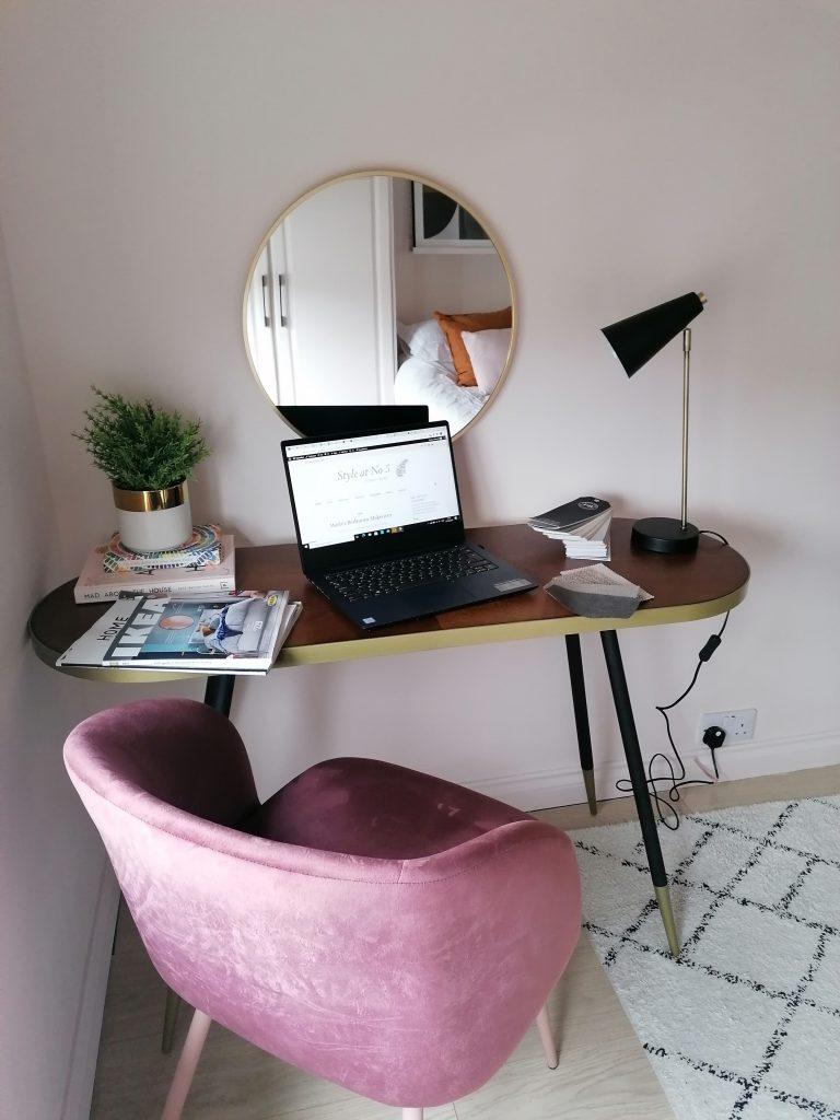 Bedroom desk set up, desk, dark pink chair, mirror, table lamp and laptop open.