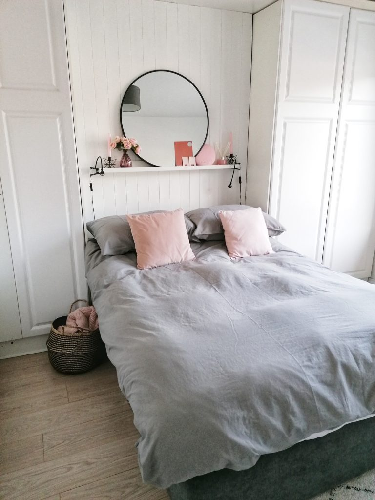 white laminate wardrobes in master bedroom with grey and pink bed clothes