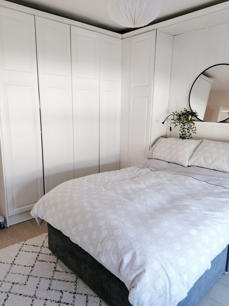 white wardrobes master bedroom with white and grey bed clothes and plants and mirror above the bed