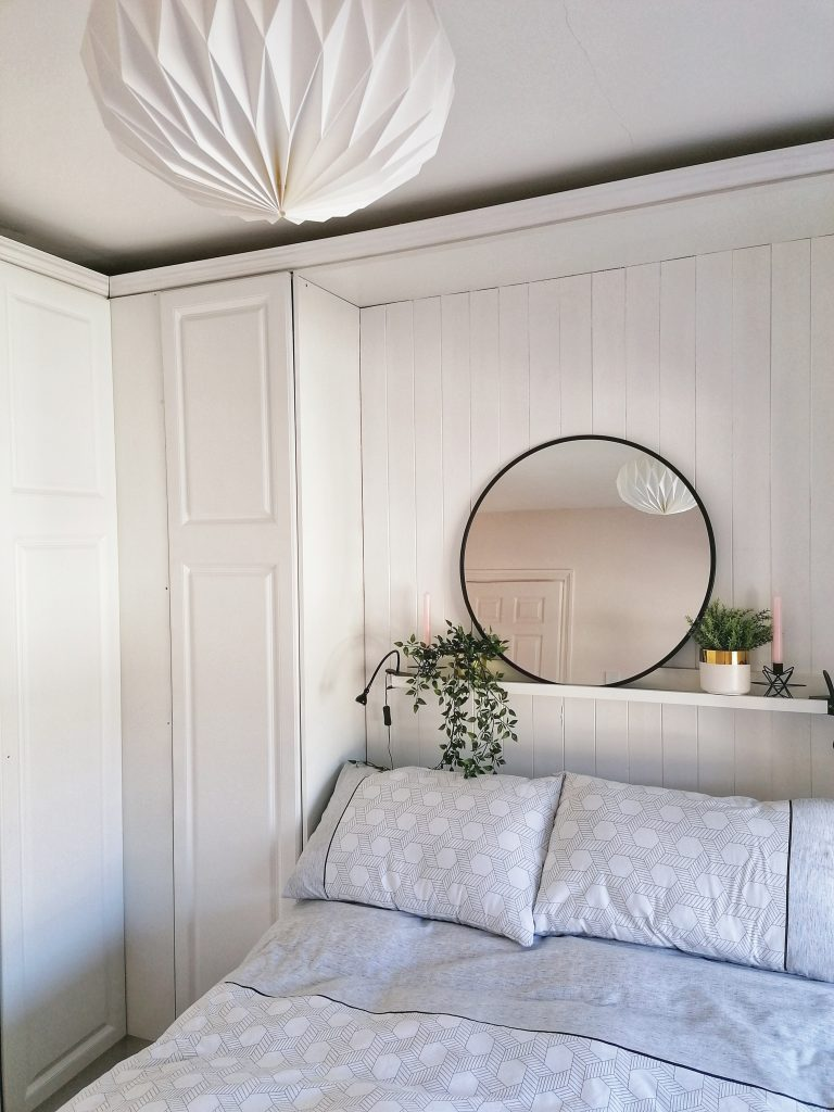 close up of bed and mirror above it with white and grey bed clothes