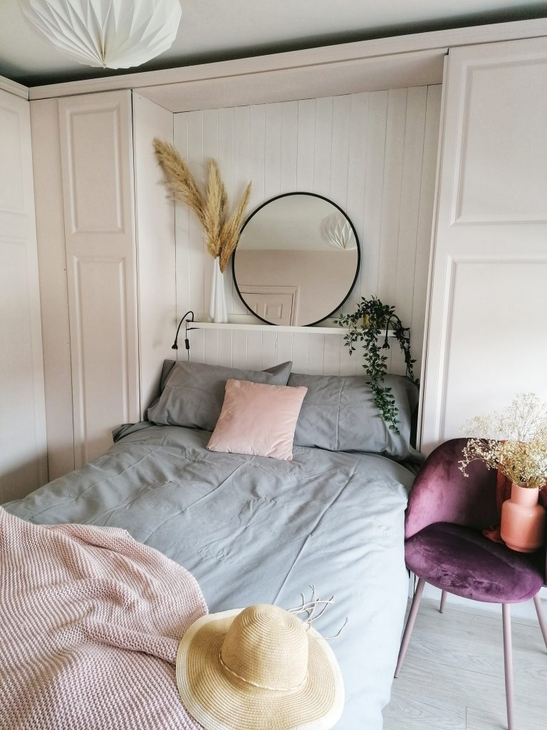 styled bedroom with pink wardrobes and white behind the bed