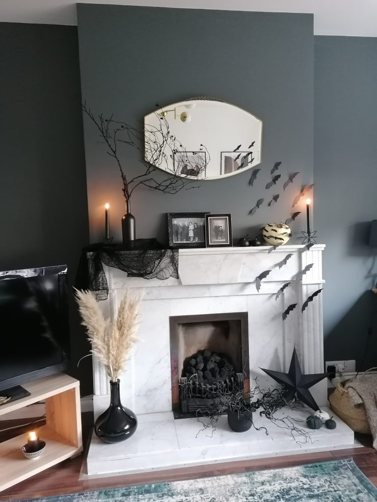 Decorated fireplace and mantel with black paper bats for Halloween