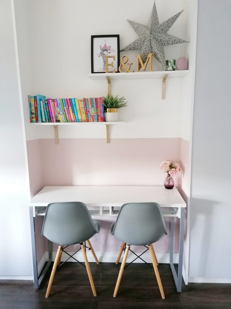 Pink wall and desk with two grey chairs