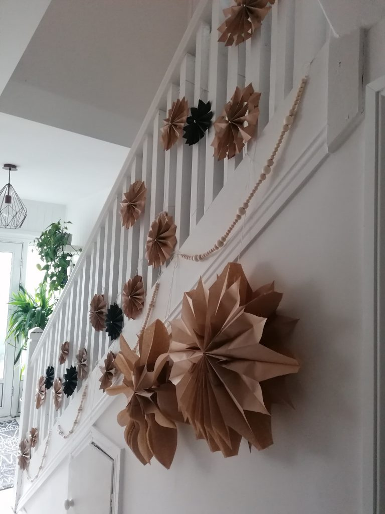 paper stars and wooden beaded garlands hanging on a staircase