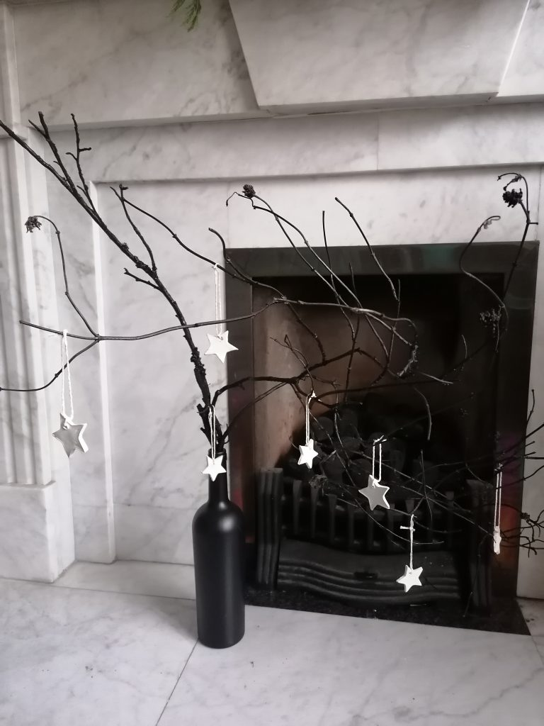 black branches in a spray painted wine bottle with little white stars made out of air dry clay