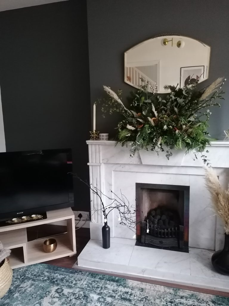 sitting room scene with mantel display and black branches and black wine bottle with air dry clay decorations hanging on the branches