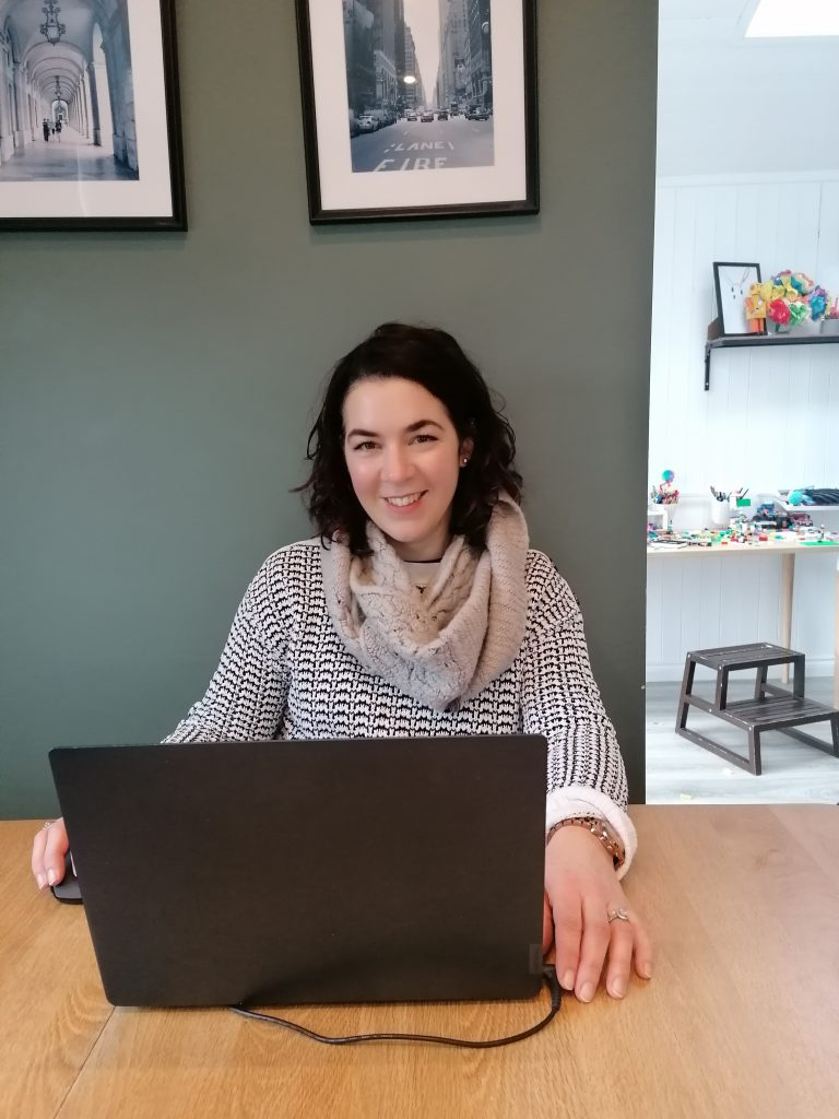 Celine Gill, Interior Designer, Style At No.5 Interior Design sitting at her laptop in the kitchen