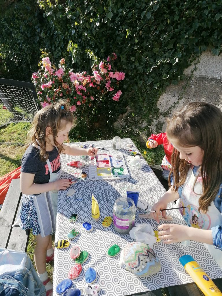 Kids painting dough Easter eggs and stones outside in the sunshine