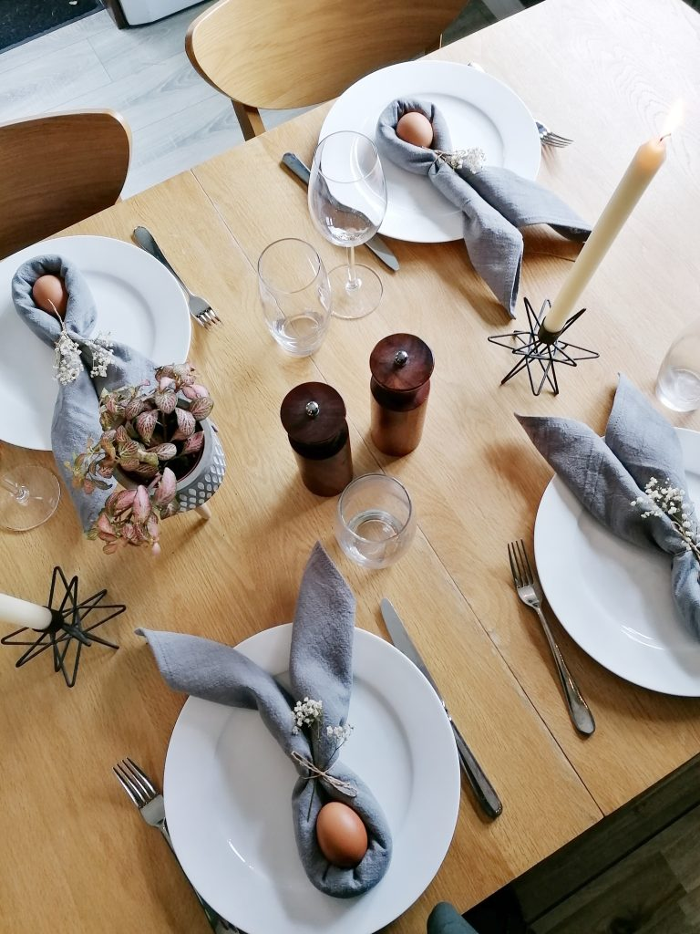Easter table decorated with napkin bunny ears and plants and candles