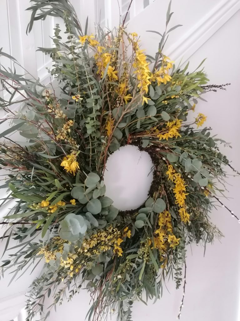 White Dove Nurseries Easter Spring wreath hanging indoors with white walls