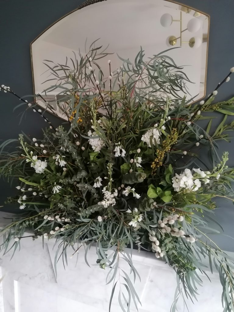 Easter display on mantelpiece with flowers and greenery