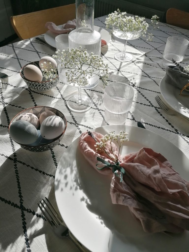 Table setting with sun shining on it and glasses and baby's breath
